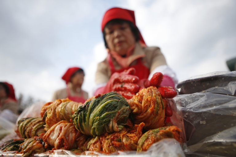 A woman makes traditional Korean side dish kimchi, or fermented cabbage, during the 2014 Seoul Kimchi Making and Sharing Festival at Seoul City Hall Plaza in Seoul November 14, 2014. More than 2,300 volunteers made 250 tonnes of kimchi on Friday to give away to needy people during the winter season.   REUTERS/Kim Hong-Ji (SOUTH KOREA - Tags: FOOD SOCIETY) - RTR4E3RR