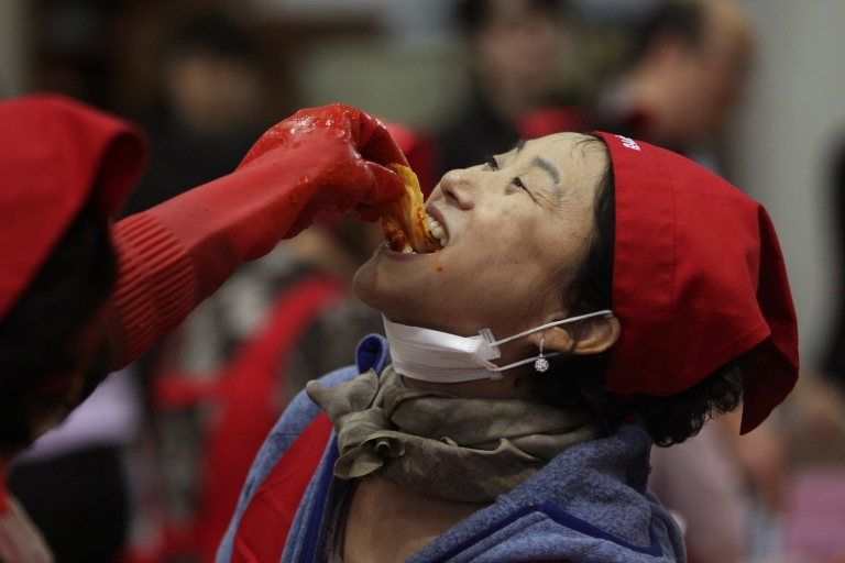 An unidentified woman tastes of kimchi, traditional pungent vegetable, to donate to needy neighbors for winter preparation at a government building in Seoul, South Korea, Wednesday, Oct. 28, 2015. About 100 volunteers made 5,500kg of kimchi. Made with cabbage, other vegetables and chili sauce, kimchi is the most popular traditional food in Korea.(AP Photo/Ahn Young-joon)