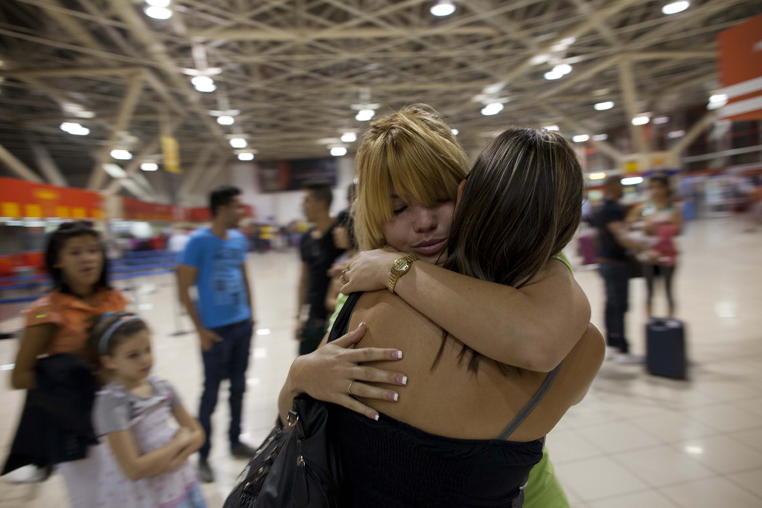 In this photo taken Jan. 30, 2013, Amalia Reigosa, hugs her sister Jaynet goodbye at the Jose Marti International Airport in Havana, Cuba, before her trip to Milan, Itlay. Reigosa was one of the first Cubans to take advantage of a travel reform that went into effect a year ago this week, when the government scrapped an exit visa requirement that for five decades had made it difficult for most islanders to go abroad. (AP Photo/Ramon Espinosa)
