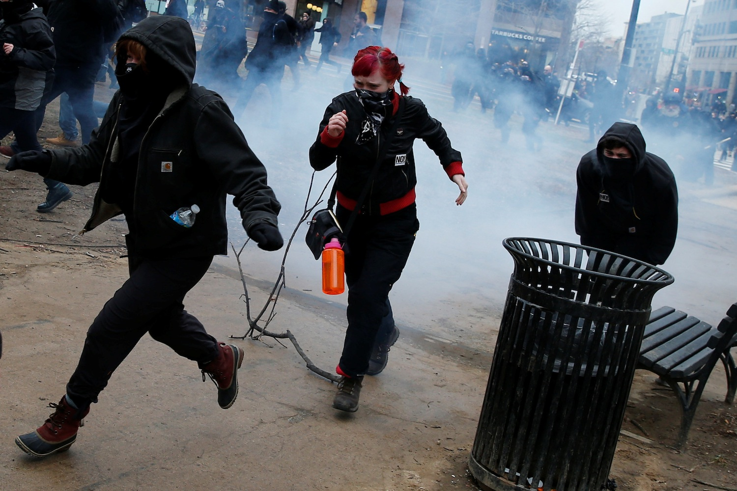 Activists run after being hit by a stun grenade while protesting against U.S. President Donald Trump on the sidelines of the inauguration in Washington, DC, U.S., January 20, 2017. REUTERS/Adrees Latif