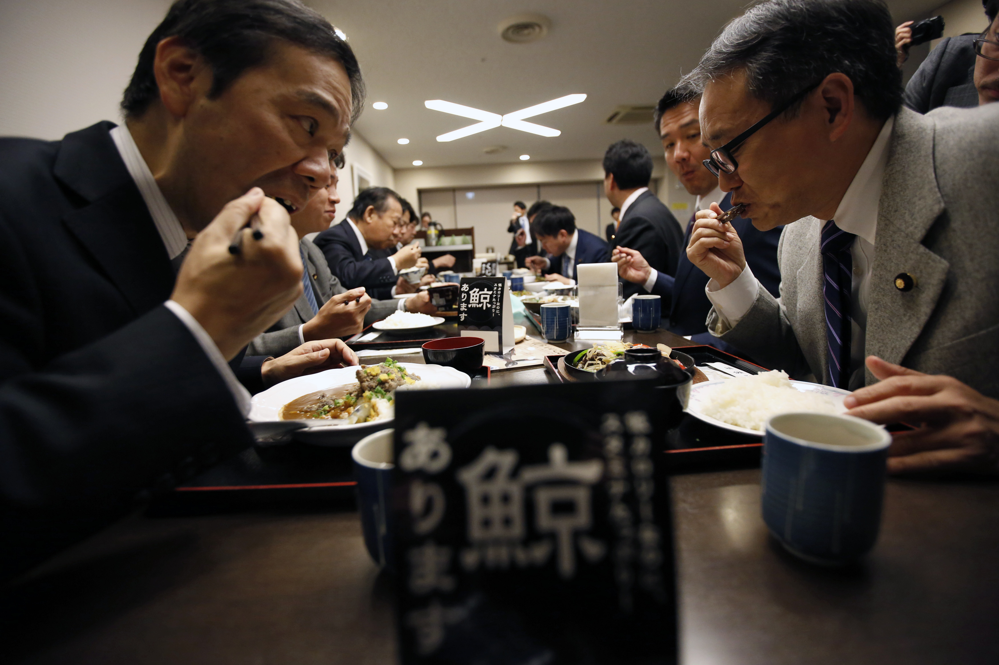 "Japanese lawmakers including Toshihiro Nikai (3rd L), former Economy, Trade and Industry Minister, and Daishiro Yamagiwa (3rd R, back toward camera), State Minister of Economy, Trade and Industry, taste whale meat menu during a whale meat promotion event at a restaurant in the ministry in Tokyo November 19, 2014. Japanese government officials lunched on whale meat on Wednesday in a bid to promote Japan's new plan to resume whale hunting in the Southern Ocean, ruled out once by the International Court of Justice (ICI) earlier this year. Japan on Tuesday unveiled plans to resume whale hunting in the Southern Ocean despite an international court ruling that previous hunts were illegal, but said it would slash the quota for the so-called scientific whaling programme. The small placard on the table (C) reads: ""Whale meat available here"". (Foto: Issei Kato/Reuters)"